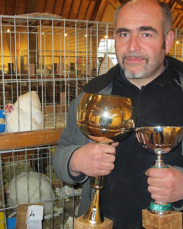 un monsieur qui porte de coupe avec des poules dans des cages derrière