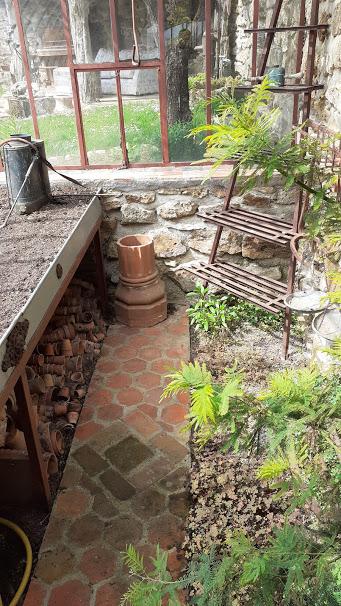 une aile de la serre, une table et un pulvérisateur en cuivre
